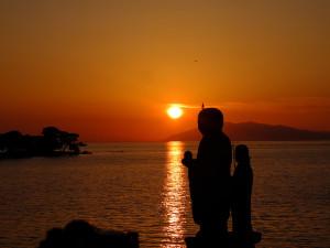 Sunset over Shinjiko Lake with Yomegashima and the budda statues